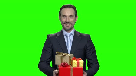 dát : Happy smiling businessman with gifts. Green hromakey background for keying.