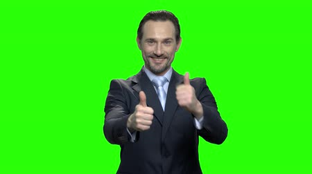 egyetért : Happy caucasian businessman showing thumbs up. Green hromakey background for keying.