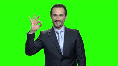 fegyelem : Portrait of a smiling adult man looking and showing you ok sign. Green hromakey background for keying.