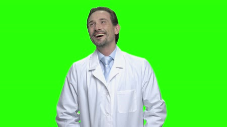 hromakey : Portrait of happy male doctor laughing hard. Funy joke. Green hromakey background for keying. Stock Footage