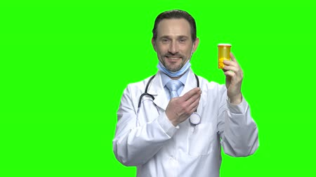 physician : Doctor advertising pills. Portrait of mature male middle aged doctor pointing at bottle of pills. Green screen hromakey background for keying.