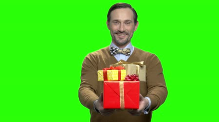 dávat : Mature caucasian man giving birthday presents. Green screen hromakey background for keying.