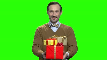 red tape : Nice handsome smiling man giving gift boxes. Green screen hromakey background for keying.