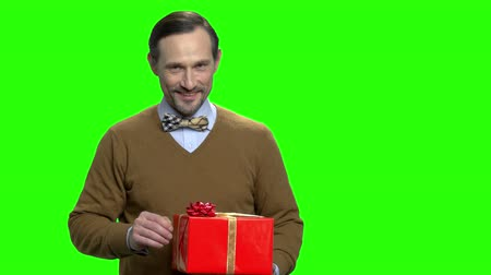 red tape : Caucasian man showing gift box. Portrait of handsome middle aged man with present. Green screen hromakey background for keying. Stock Footage