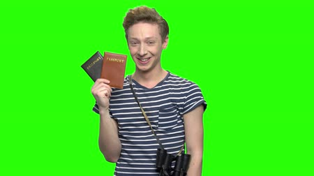 keying : Young tourist boy with shows passports. Green screen hromakey background for keying.