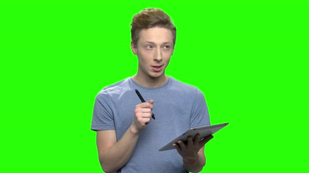 keying : Teenager writing in tablet using pen. Green screen hromakey background for keying. Stock Footage