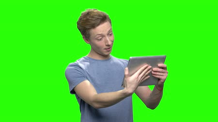 idéia genial : Positive teenager boy holds tablet PC. Facial expressions. Green screen hromakey background for keying.
