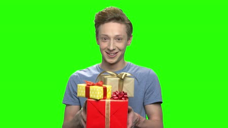 deha : Portrait of teenage boy giving present gift boxes. Green screen hromakey background for keying.