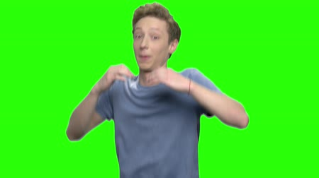 chmiel : Teenager boy dancing and enjoying music. Green screen hromakey background for keying.