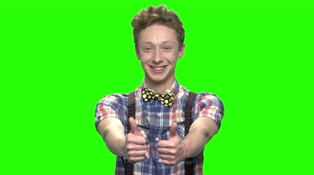 idéia genial : Portrait of handsome boy with two thumbs up. Green screen hromakey background for keying.