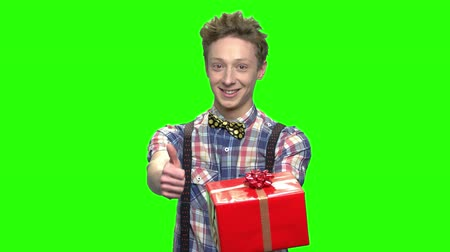 obrigado : Young boy giving gift box and thumb up. Thank you for gift concept. Green screen hromakey background for keying. Vídeos