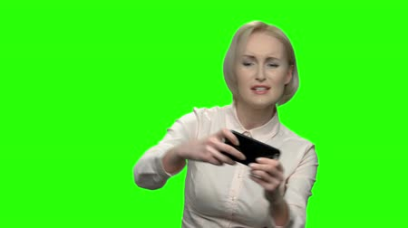 hromakey : Middle aged businesswoman playing video games on her phone. Excited enthusiastic blonde woman. Green screen hromakey background for keying.