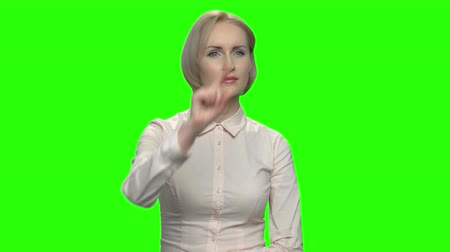 hromakey : Beautiful mature sexy woman using virtual screen. Invisible imaginary virtual interface, green background for keying. Stock Footage
