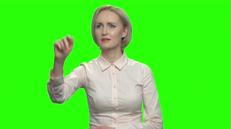 imaginário : Woman in business shirt working with invisible virtual reality screen. Green screen hromakey background for keying.