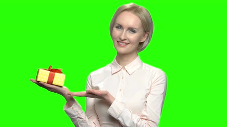 hromakey : Portrait of mature woman with gift box. Yellow present box and red ribbon. Green hromakey background for keying. Stock Footage