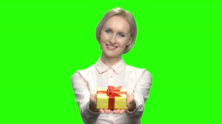 keying : Portrait of caucasian woman giving gift box. Blond mature business woman. Green hromakey background for keying. Stock Footage