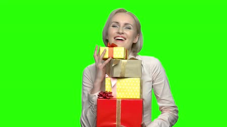 продвигать : Mature woman recieved many gift boxes for her birthday. Green hromakey background for keying.