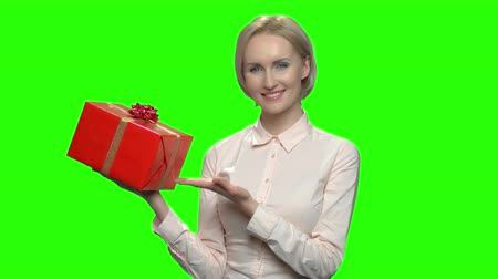 prémie : Woman pointing at red gift box. Green hromakey background for keying.