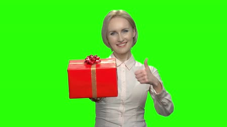 darovat : Businesswoman with red gift box and thumb up. Green hromakey background for keying. Dostupné videozáznamy