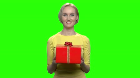 dát : Beautiful adorable woman holding red gift box. Long sleeve yellow tshirt. Green hromakey background for keying.