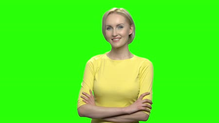 сложены : Portrait of beautiful blond woman with folded arms. Mature middle aged happy smiling female in yellow tshirt. Green hromakey background for keying.