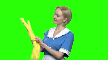 hromakey : Woman cleaner puts on rubber gloves. Green hromakey background for keying.