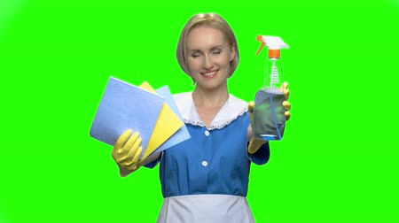 püskürtücü : Cleaning woman shows bottle spray and napkins. Green hromakey background for keying. Stok Video