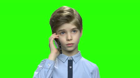 schoolkid : Toddler boy talking on the phone with parents. Green hromakey background for keying.