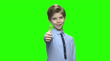 schooljongen : Little boy giving thumb up. Green hromakey background for keying.