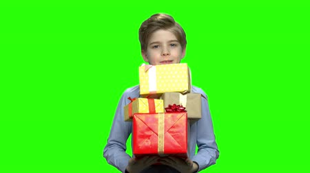 продвигать : Portrait of little boy holding lots of gift boxes in his two arms. Green hromakey background for keying. Стоковые видеозаписи