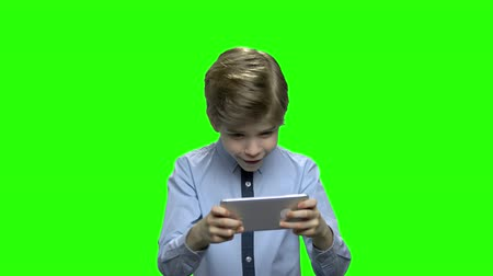 schoolkid : Portrait of a cute little kid playing games on smartphone. Green hromakey background for keying. Stock Footage