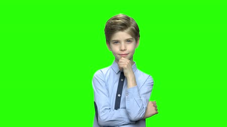 hromakey : Cute pensive little boy in blue shirt. Green hromakey background for keying.
