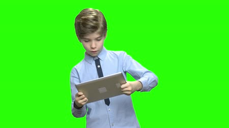 nesiller : Children with tablet PC playing games. Boy holding modern gadget device and playing video games. Green hromakey background for keying. Stok Video