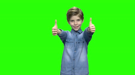 hromakey : Cute child boy in denim jacket showing two thumbs up. Green hromakey background for keying.