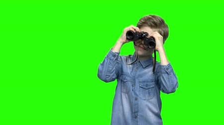 gözlem : Child boy tourist looking through binoculars. Green hromakey background for keying. Stok Video