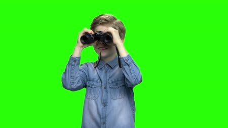 brim : Little boy in denim jacket observing locations using binoculars. Green hromakey background for keying.