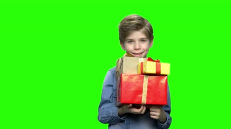 karácsonyi ajándék : Portrait of little boy in denim jacket with gift boxes. Green hromakey background for keying.