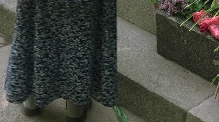 memorial day : Old lady feet. Put flwoers on memorial stone. Stock Footage