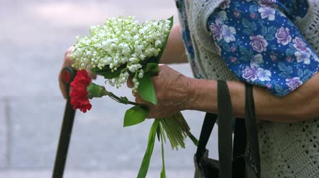 tribute : Old senior grandma with flowers during memorial day. Close up. Very old lady with stick, flowers and bag.
