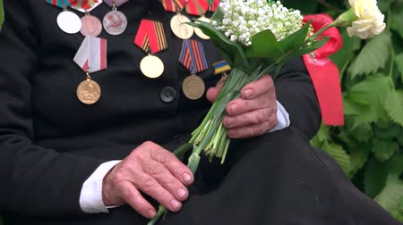 sleeve : Old war veteran with flowers and medals. 9 may, victory day. Close up.