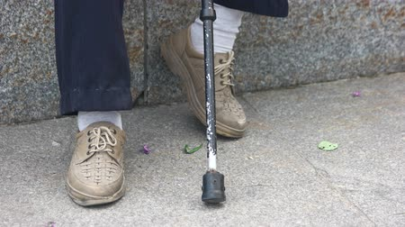 poorness : Old man feet and cane. Close up.