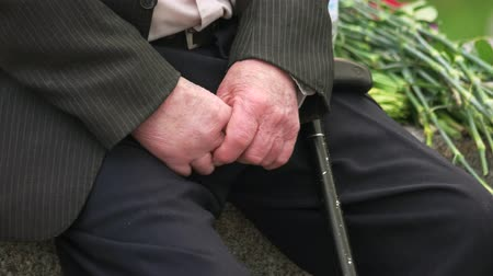 sleeve : Senior male veteran with cane stick. Close up. Black pants and jacket.
