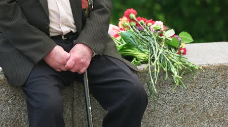 důchodce : Old senior veteran with cane and flowers. Close up. Veteran of world war, memorial day.