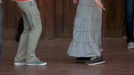 close cropped : Dancing couple legs close up. Rustic wooden background.