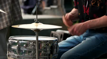 perkusja : Young man plyaing on drums in a rock band. Close up hands with drum sticks.