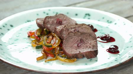 dana eti : Veal with cherry sauce. Roasted meat and vegetables.