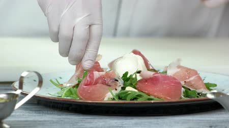 kesudió : Hand adding ingredient to salad. Arugula, prosciutto and cashew nut.