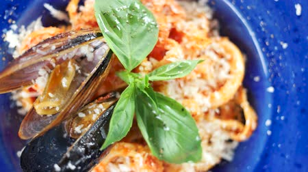 seafood recipe : Pasta dish macro. Garnished food, basil leaf.