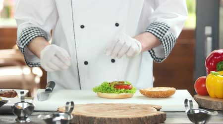 соленья : Hands of chef making burger. Lettuce leaves and onion. Healthy fast food options.
