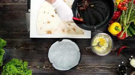 taco : Hands making burrito top view. Tortilla, fried meat and vegetables. Stock Footage